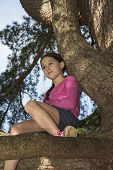 image of daydreaming  - Girl climbs to the top of an old tree on a beautiful spring day. Relaxing in a daydream - JPG