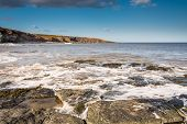 image of shoreline  - Incoming tide flowing over the rocky shoreline at Cullernose Point on the Northumberland coast - JPG