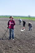 picture of hoe  - Senior peasant with hoe standing on fertile land other peasants hoeing and sowing in background - JPG