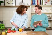 image of wifes  - Portrait of a husband and wife reading recipe from tablet - JPG