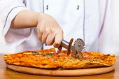 picture of chef knife  - chef with knife cuts the pizza closeup - JPG