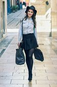stock photo of mini-skirt  - Beautiful brunette young woman wearing short skirt and denim shirt walking on the street with shopping bags - JPG