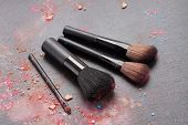 Picture of set of make up brushes with make up crumbles on black background.