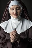 stock photo of cross-dress  - Young catholic nun holding cross in her hands - JPG