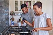 foto of morning  - young couple preparing early morning eggs breakfast on stove in home kitchen - JPG