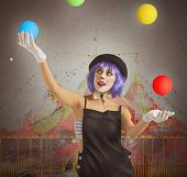 picture of clowns  - Concentrated juggler clown playing with colorful ball - JPG