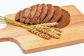 foto of malt  - Slices of rye malt bread and wheat ears on the chopping board - JPG