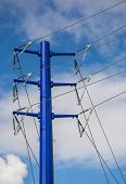stock photo of transmission lines  - Blue transmission tower and high voltage power lines with a blue sky and white cloud background - JPG