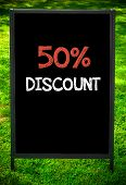 pic of fifties  - FIFTY PERCENT DISCOUNT message on sidewalk blackboard sign against green grass background - JPG