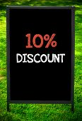 image of ten  - TEN PERCENT DISCOUNT message on sidewalk blackboard sign against green grass background - JPG