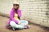 stock photo of snickers  - Blond teenage girl in jeans and sunglasses sits on her skateboard near urban brick wall photo with warm retro tonal correction effect instagram old style filter - JPG