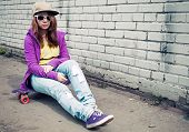 pic of snickers  - Blond teenage girl in jeans and sunglasses sits on her skateboard near urban brick wall photo with cold retro tonal correction effect instagram old style filter - JPG