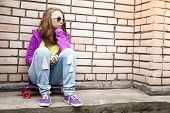 pic of snickers  - Blond teenage girl in a sunglasses sits on her skateboard near urban brick wall photo with retro tonal correction instagram old style filter - JPG