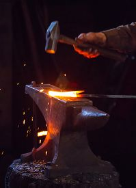 picture of anvil  - Blacksmith hammering a hot metal rod on an anvil - JPG
