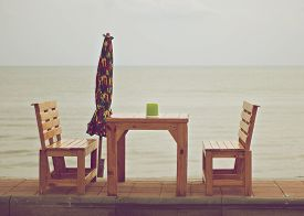 stock photo of tissue box  - Green tissue box on wood table with colorful umbrella beside the sea in vintage style - JPG