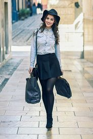 stock photo of denim wear  - Beautiful brunette young woman wearing short skirt and denim shirt walking on the street with shopping bags - JPG