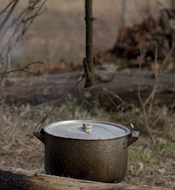 stock photo of smut  - Cooking in old sooty cauldron on campfire at forest - JPG