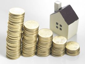 stock photo of house representatives  - Model house on a stack of coins representing high prices on real estate market - JPG