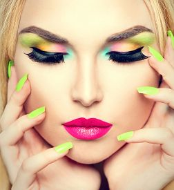foto of colore  - Beauty Woman face Portrait with Vivid Makeup and colorful Nail polish - JPG