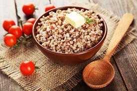 image of buckwheat  - Buckwheat in bowl on brown wooden background - JPG