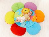 Happy baby lying on colorful flower playmat, smiling, elevated view.?