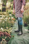 Gardener In Apron And Rubber Boots With Pruning Shears In Hand Standing In Garden poster
