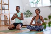 Calm relaxed couple meditating at home doing yoga relaxation poster