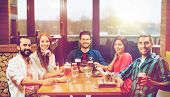 leisure, eating, food and drinks, people and holidays concept - smiling friends having dinner and dr poster