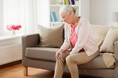 old age, health problem and people concept - senior woman suffering from pain in leg at home poster