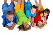 image of happy kids  - A group of children lie down in the studio grinning as they pose together - JPG