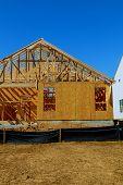 wood framework of new residential home under construction. Home Under Construction