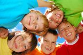 stock photo of huddle  - Happy sisters with brothers forming a huddle - JPG