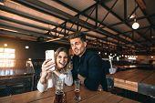 Couple Taking Selfie On Mobile Phone Inside The Bar poster