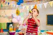 Cute boy blowing party horn during birthday party at home poster