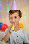 Boy blowing a party horn during birthday party at home poster