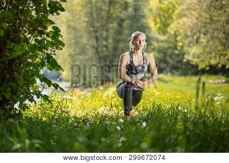 poster of Young, Blonde Fit Woman In Black Sports Tights Doing Her Training In The Nature By The River. Fitnes