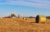 Autumn Rural Landscape With Blue Sky Over Stubble Field And Hay Bales On A Foreground And Farm Build poster