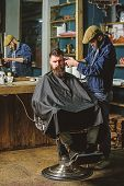 Hipster Client Getting Haircut. Barber With Clipper Trimming Hair On Temple Of Client. Barber With H poster