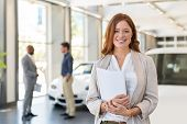 Smiling saleswoman holding document while looking at camera at car showroom. Cardealer holding clipb poster