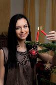 young woman with christmas tree lights on christmas candle