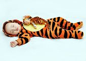 A Small Child In A Tiger Costume Is Sleeping Next To A Doll. A Little Girl And Her Favorite Doll Are poster