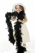 A beautiful preschooler dressed all in white, except for a long, feathery black boa draped over her shoulders.  On a white background.