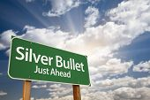 stock photo of fail-safe  - Silver Bullet Just Ahead Green Road Sign with Dramatic Clouds - JPG