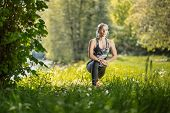 Young, Blonde Fit Woman In Black Sports Tights Doing Her Training In The Nature By The River. Fitnes poster