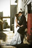 Newlyweds Kissing Passionately Against A Red Box