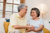 Asian Elderly Couple Holding Their Hands While Taking Together In Living Room, Couple Feeling Happy  poster