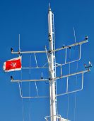 stock photo of maltese-cross  - The radio mast of the ferry between Gozo and Malta with the flag showing the Maltese Cross blowing briskly - JPG