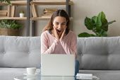 Woman Sitting On Couch Reading Received Email Feels Surprised Amazed poster