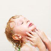 Niña, lavar la cara en el baño