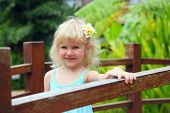 Beautiful little girl with a tropical flower plumeria